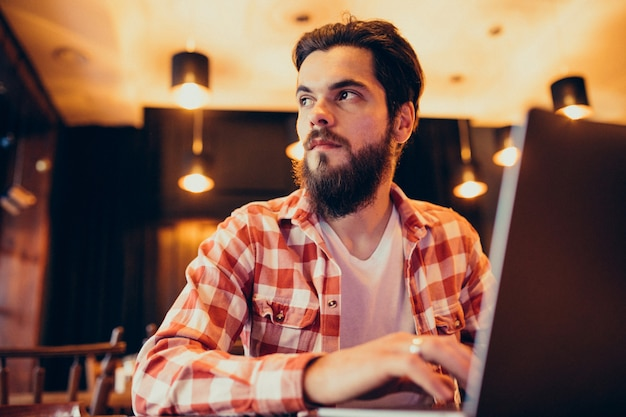 Youn g bearded man working on laptop in a bar