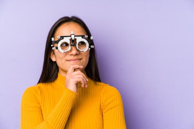 Молодая индийская женщина в очках оптометрии смотрит в сторону с сомнительным и скептическим выражением лица.