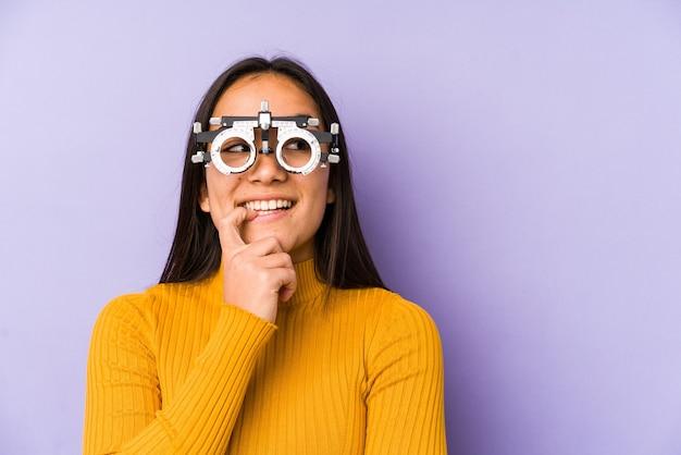 Молодая индийская женщина в очках оптометрии расслабилась, думая о чем-то, глядя на копировальное пространство.