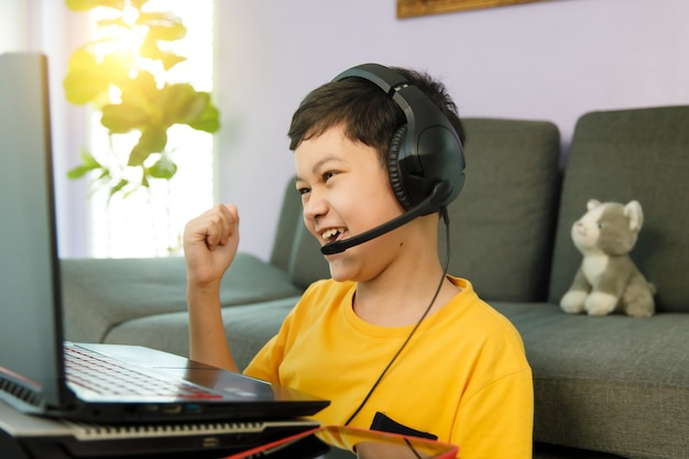 Youn little cute asian 10s boy wearing headphones sitting in home living room using laptop notebook computer for online distance study and rise fist punch with excited and self-confident