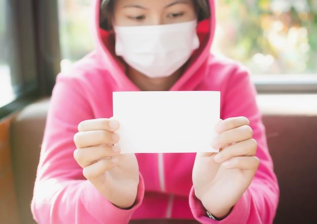 空白の白い正方形のチラシパンフレットの小冊子を示す若い女性。