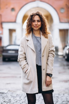 Youn woman with curly hair outside the street