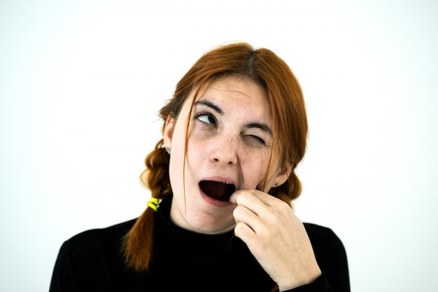 Youn woman with open mouth digging with her fingers for something stuck in teeth after eating.