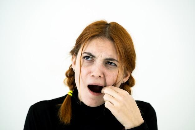 食べて歯に刺さった何かのために口を掘って指を掘るyoun女性。