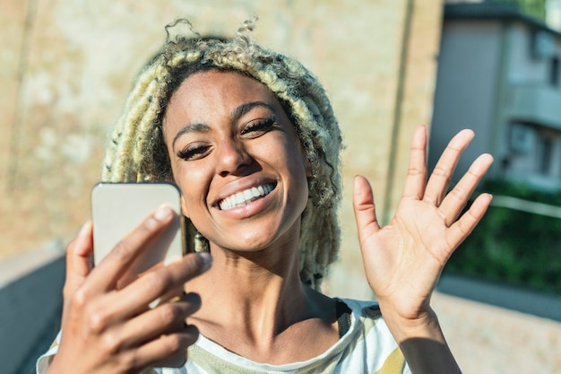 Yound african woman with blond dreadlocks doing video call with smart mobile phone