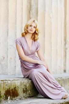 Молодая и красивая блондинка в длинном платье возле колонн