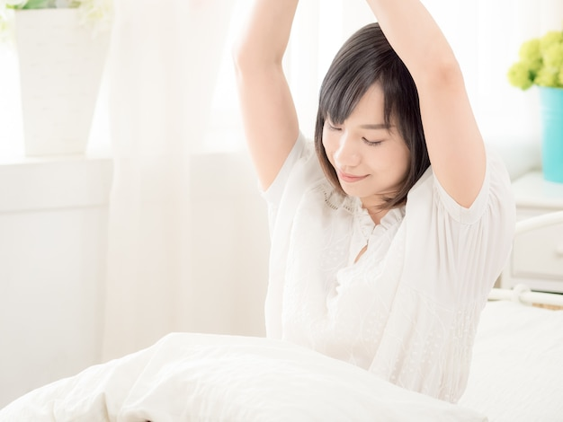 Yound asian girl waking up stretching arms on the bed in the morning.