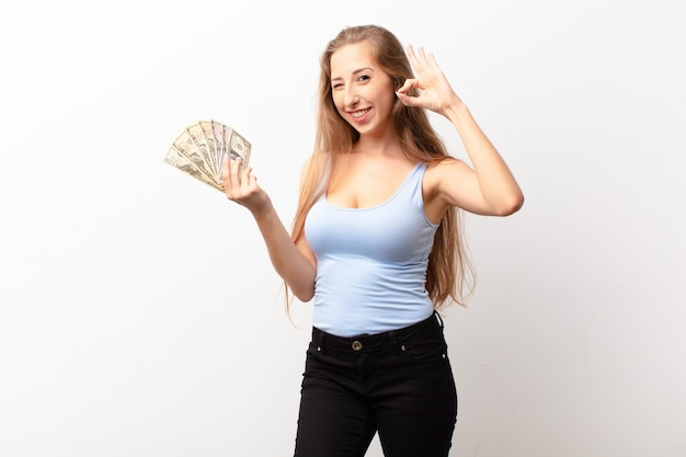 Yound blonde woman feeling happy, relaxed and satisfied, showing approval with okay gesture, smiling holding dollar banknotes