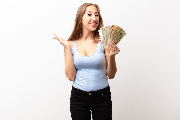 Yound blonde woman feeling happy, surprised and cheerful, smiling with positive attitude, realizing a solution or idea holding dollar banknotes