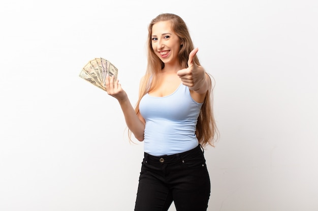 Yound blonde woman feeling proud, carefree, confident and happy, smiling positively with thumbs up holding dollar banknotes