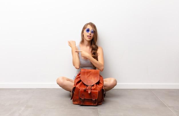 Молодая блондинка выглядит нетерпеливой и сердитой, указывая на часы, прося пунктуальности, хочет вовремя сесть на пол