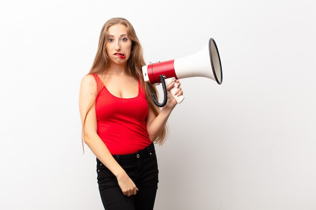 Yound blonde woman looking puzzled and confused, biting lip with a nervous gesture, not knowing the answer to the problem holding a megaphone