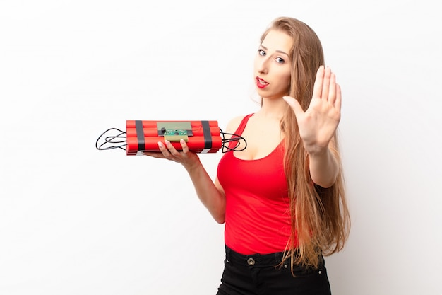 Yound blonde woman looking serious, stern, displeased and angry showing open palm making stop gesture holding a dynamite bomb