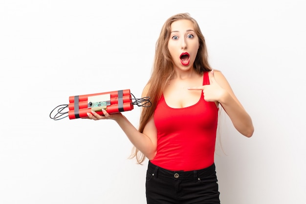 Yound blonde woman looking shocked and surprised with mouth wide open, pointing to self holding a dynamite bomb