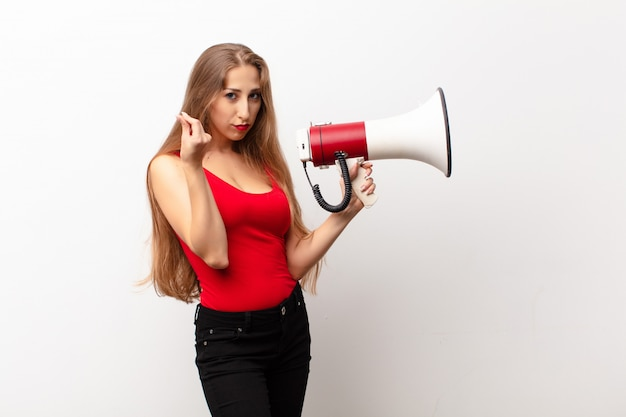 Yound blonde woman making capice or money gesture, telling you to pay your debts! holding a megaphone