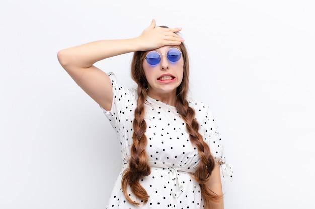 Молодая белокурая женщина, паникующая из-за забытого срока, испытывающая стресс, вынужденная скрывать беспорядок или ошибку на фоне белой стены