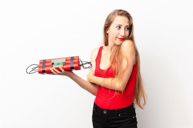 若い金髪女性が肩をすくめて、混乱して不確実に感じ、腕を組んで困惑した表情でダイナマイト爆弾を保持していると疑う