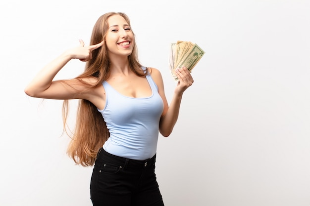 Yound blonde woman smiling confidently pointing to own broad smile, positive, relaxed, satisfied attitude holding dollar banknotes