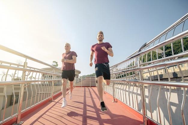 橋を渡って走っている若い男性と成熟した白髪の男性