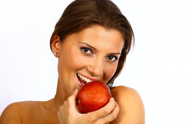 新鮮な赤いリンゴを保持している若い女性