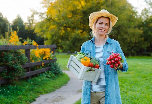 庭で新鮮な生態学的な野菜の箱と帽子の若い30-35歳の美しい女性農家