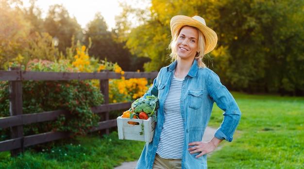新鮮な生態学的な野菜の箱と帽子の若い30-35歳の美しい女性農家
