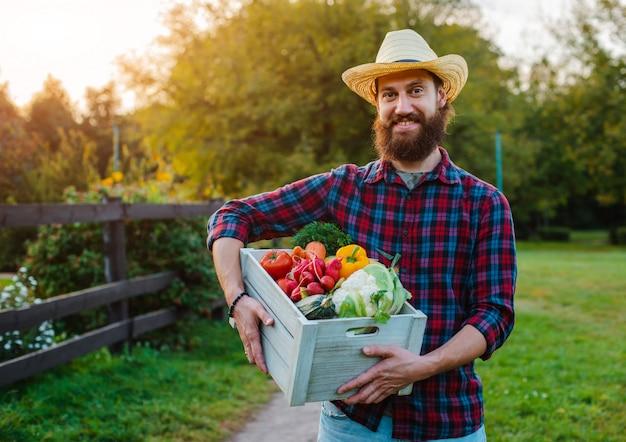 若い30-35歳若いひげを生やした男性男性農家の帽子ボックスと新鮮な生態学的な野菜の庭