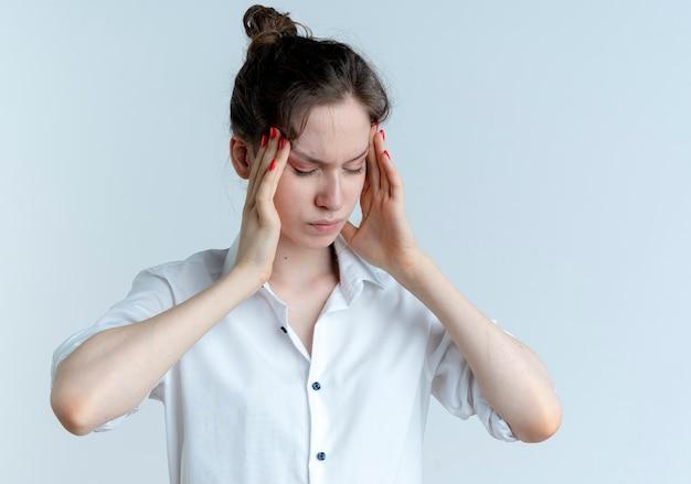 若い痛むブロンドのロシアの女の子は、コピースペースで白いスペースに分離された目を閉じて頭を保持します