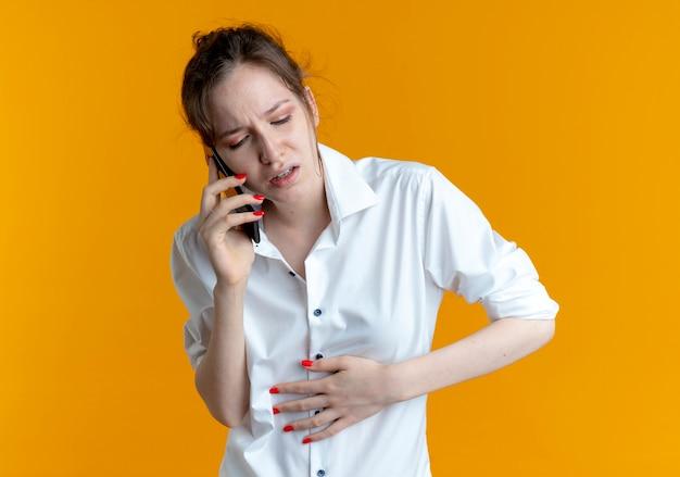La giovane ragazza russa bionda dolorante mette la mano sulla pancia che parla sul telefono isolato sullo spazio arancione con lo spazio della copia