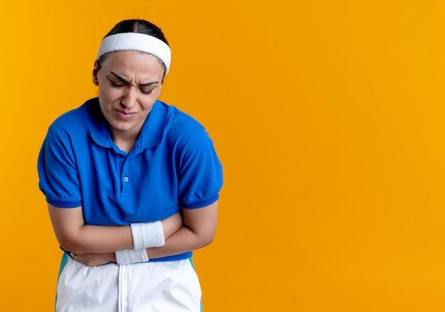 머리띠와 팔찌를 착용하는 젊은 아프다 백인 스포티 한 여자는 복사 공간 오렌지에 배꼽을 보유하고