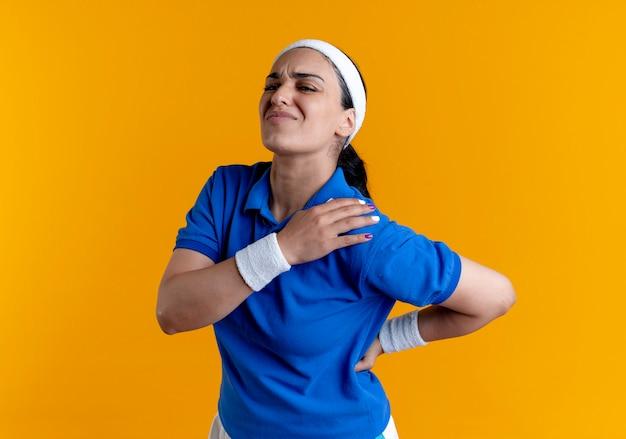 ヘッドバンドとリストバンドを身に着けている若い痛む白人スポーティな女性は、コピースペースでオレンジ色の背景に分離された肩と背中を保持します