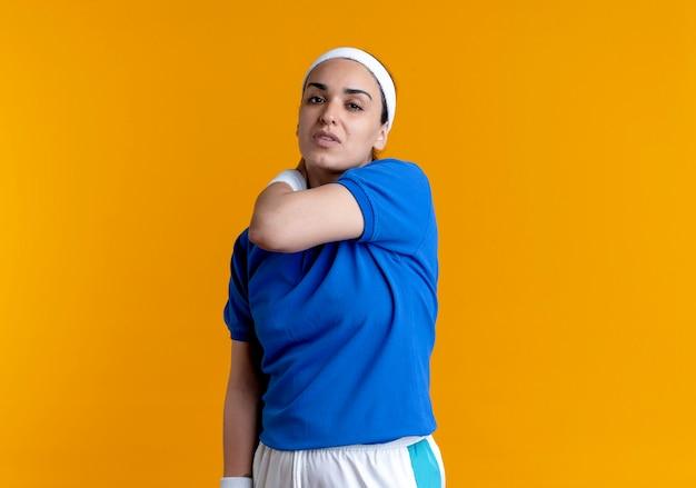 머리띠와 팔찌를 착용하는 젊은 아프다 백인 스포티 한 여자는 복사 공간이 오렌지 뒤에서 어깨를 보유하고