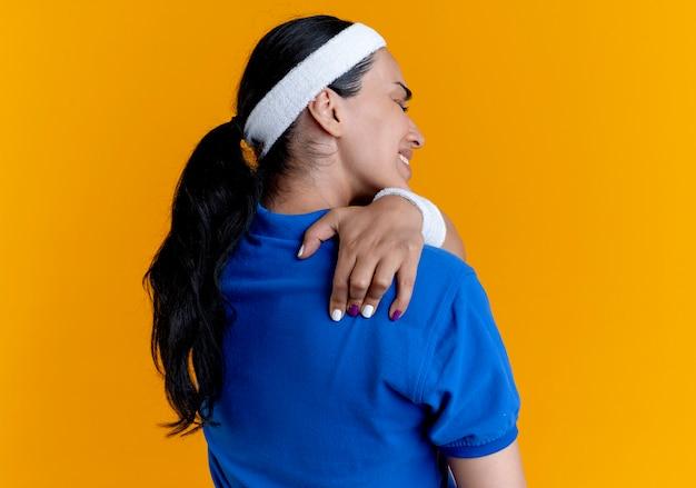 머리띠와 팔찌를 착용하는 젊은 아프다 백인 스포티 한 여자가 다시 카메라에 서서 복사 공간이 오렌지 공간에 고립 된 어깨를 보유하고 있습니다.