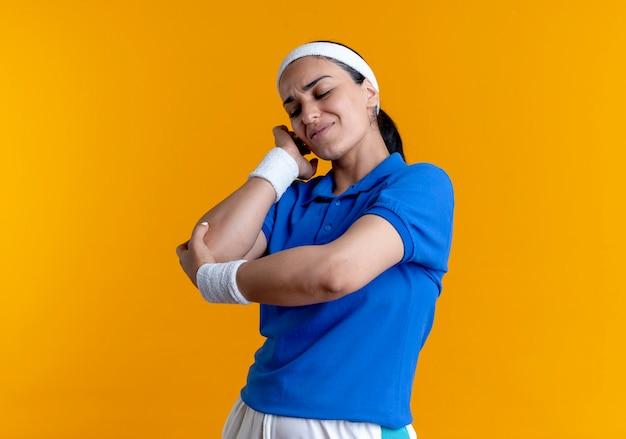 La giovane donna sportiva caucasica dolorante che indossa la fascia ed i braccialetti tiene il gomito sull'arancia con lo spazio della copia