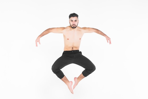 Young, acrobat man doing exercise  in the air
