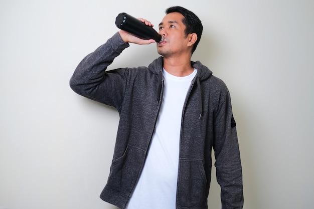 스포츠 후 텀블러에서 물을 마시는 젊은 활동적인 아시아 남자