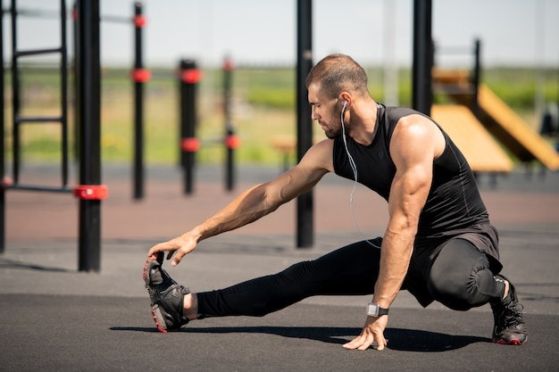 Young active athlete in black tracksuit stretching his right arm and leg while exercising on outdoor sportsground