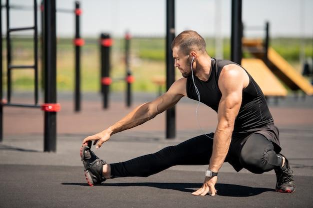 Молодой активный спортсмен в черном спортивном костюме растягивает правую руку и ногу во время тренировки на открытой спортивной площадке