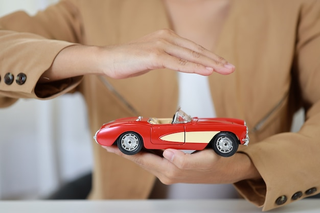 Молодая активная бизнес-леди вручает в повседневном платье сидя, удерживая и защищая модель автомобиля или автомобиль на белом столе.