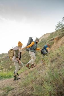 수염 난 남자가 자연 환경에서 여행하는 동안 아내와 아들을 돕는 동안 배낭을 메고 위쪽으로 이동하는 젊은 활동적인 가족