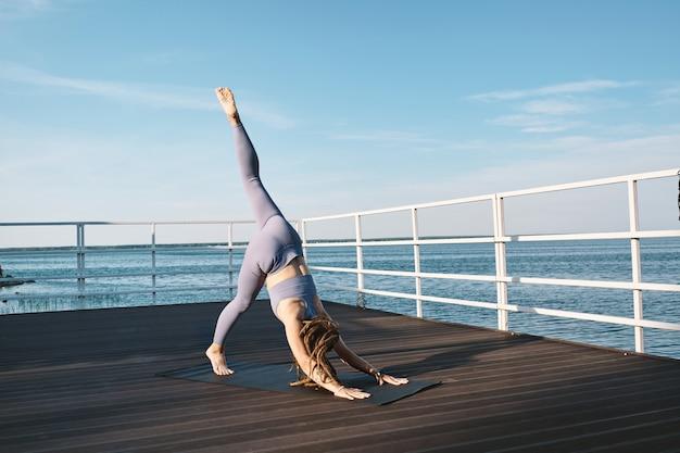 左足を上げたまま前屈する若いアクティブな女性