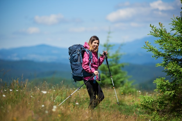 Young active female climber with backpack and trekking sticks, trekking in the mountains, enjoying sunny day. concept of active lifestyle