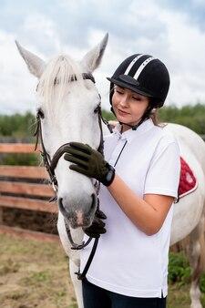 Молодая активная самка обнимает морду белой породистой скаковой лошади или кобылы во время холода в сельской местности