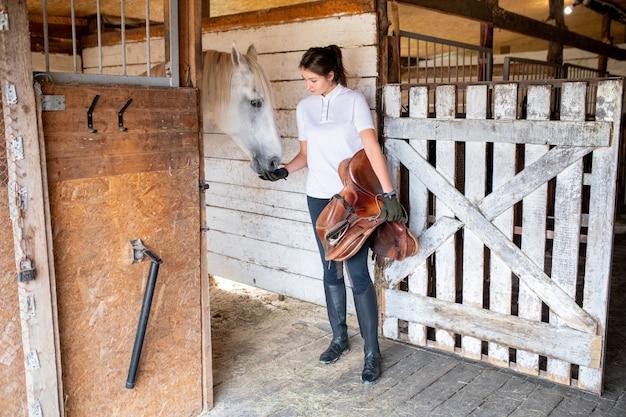 Молодая активная женщина в рубашке поло, узких джинсах, черных кожаных ботинках и перчатках стоит возле конюшни и кормится скаковой лошадью