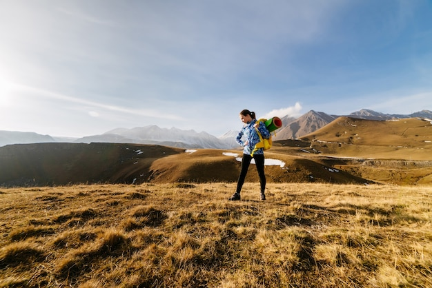 A young active girl in a blue jacket travels through the caucasus mountains with a backpack and tent