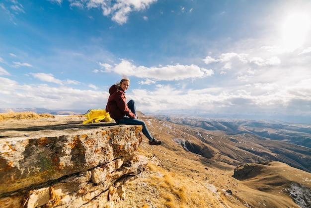 若いアクティブな女の子の旅行者は、崖の端に座って、きれいな山の空気と太陽を楽しんでいます