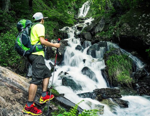배낭과 트레킹 스틱을 들고 숲속의 폭포를 바라보는 젊은 활동적인 등산객
