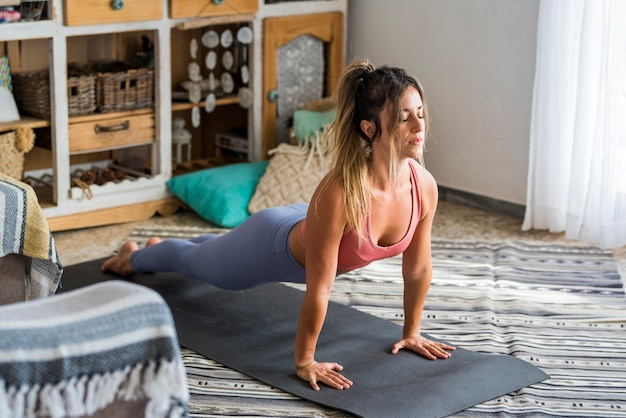 Young active lifesyle woman do push ups or plank exercise at home on the floor with mat  fitness workout indoor female people