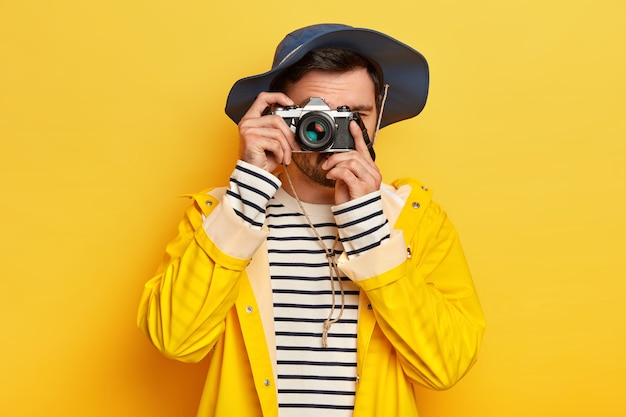 Young active male traveler takes photo with retro camera, dressed in hat, raincoat as travels during rainy day, poses against yellow wall