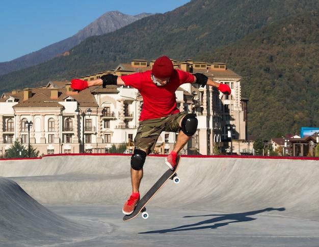 スケートパークのスケートボードでオーリートリックをジャンプする若いアクティブな男